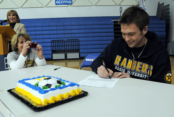 Broomfield High's Garrett Seitz, right, signs his letter of intent to Regis University while his mother Jodee takes his picture on national signing day in the Eagle Gym on Wednesday.<br /> February 3, 2010<br /> Staff photo/David R. Jennings