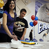 Jiana Davis, left,  helps Garrett Seitz with serving his cake during Broomfield High national signing day in the Eagle Gym on Wednesday.<br /> February 3, 2010<br /> Staff photo/David R. Jennings