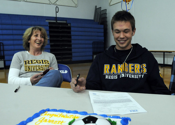 Broomfield High's Garrett Seitz, right, prepares to sign his letter of intent to Regis University while his mother Jodee watches on national signing day in the Eagle Gym on Wednesday.<br /> February 3, 2010<br /> Staff photo/David R. Jennings