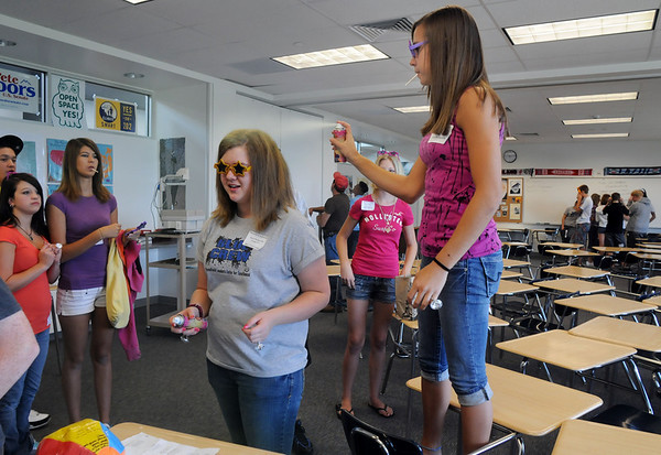 Freshman Breanne Claussen, right, sparys the hair of her leader Sara Waligorski as they prepare to tour the school during Freshman Orientation Day at Broomfield High School on Tuesday.<br /> <br /> August 18, 2009<br /> staff photo/David R. Jennings