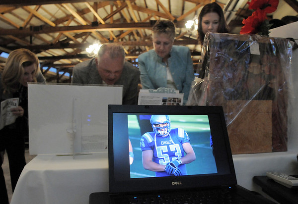 Pictures of athletes in action are shown while attendees bid for items at the auction tables at the Broomfield High School Sports Gala on Friday at the Church Ranch Events Center. <br /> March 18, 2011<br />  staff photo/David R. Jennings