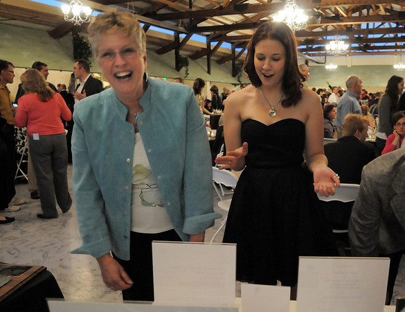 Katie Ferraro, right, asks her mother Nancy to bid on the Hawaii vacation at Broomfield High School Sports Gala on Friday at the Church Ranch Events Center. <br /> March 18, 2011<br />  staff photo/David R. Jennings