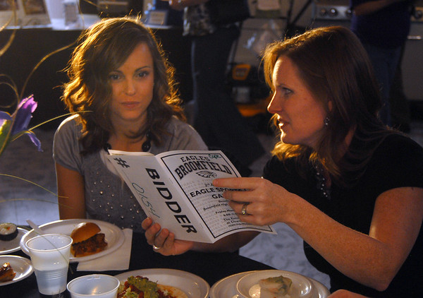 Kimberlie McBride and Stephanie Cope look at the auciton book during the Broomfield High School Sports Gala on Friday at the Church Ranch Events Center. <br /> March 18, 2011<br />  staff photo/David R. Jennings