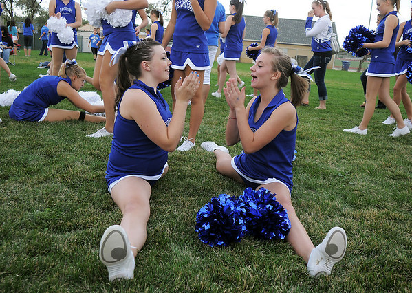 Broomfeild Poms Sarah Kochevar, 14, left and Kalia Thomas, 14, do pat-a-cake while doing the splits during warming up for their routine at the tailgate party before Friday's game against Monarch.<br /> September 16, 2011<br /> staff photo/ David R. Jennings