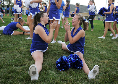 Broomfeild Poms Sarah Kochevar, 14, left and Kalia Thomas, 14, do pat-a-cake while doing the splits during warming up for their routine at the tailgate party before Friday's game against Monarch. September 16, 2011 staff photo/ David R. Jennings