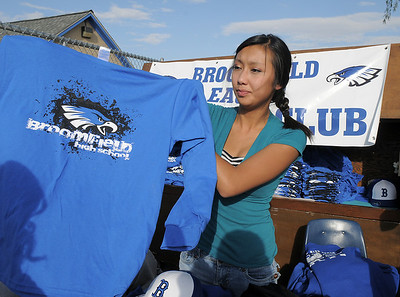 Cassandra Ho, 16, shows a long sleeved t-shirt to a customer at the Booster Club booth at the tailgate party before Friday's game against Monarch. September 16, 2011 staff photo/ David R. Jennings