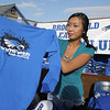 Cassandra Ho, 16, shows a long sleeved t-shirt to a customer at the Booster Club booth at the tailgate party before Friday's game against Monarch.<br /> September 16, 2011<br /> staff photo/ David R. Jennings