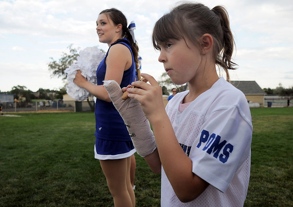 Rachel Kochevar, 9, eats a cookie while waiting for her sister Abby to perform a dance with the pom squad at the tailgate party before Friday's game against Monarch.<br /> September 16, 2011<br /> staff photo/ David R. Jennings
