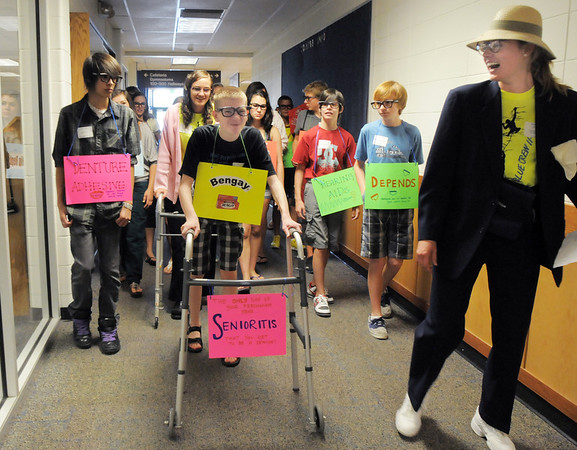 Freshman Nic Toms, center, uses a walker as a prop while touring the school lead by Blue Crew leader Kathryn Middel-Katzenmeyer, right, during freshman orientation at Broomfield High School on Monday.<br /> <br /> August 15, 2011<br /> staff photo/ David R. Jennings