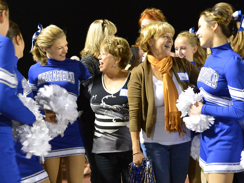 First Broomfeild High pom squad members Judy Peak Fitzsimmons, center left,  and her sister Darline Peak Head chat with current members of the school's pom squad during halftime at Friday's Broomfield High homecoming game at Elizabeth Kennedy Stadium.<br /> September 21, 2012<br /> staff photo/ David R. Jennings