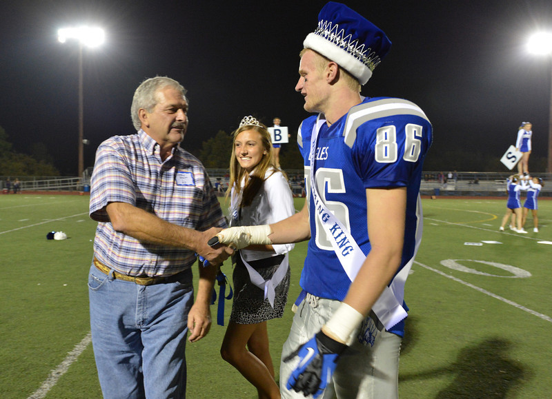 Jerre West, class of '62, left, the first homecoming king of Broomfield High greets Dan Perse, the current homecoming king with Katie Croell the current queen during Friday's Broomfield High homecoming game at Elizabeth Kennedy Stadium.<br /> September 21, 2012<br /> staff photo/ David R. Jennings