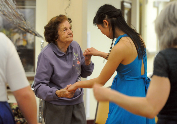 Lorraine Devling, left, and Vivian Vu, 18, teach each other dance moves during the Broomfield High School's Future Business Leaders of America and Key Club Senior Citizen Prom at Highland Trails Retirement Homes on Saturday.<br /> <br /> April 11, 2010<br /> Staff photo/David R. Jennings