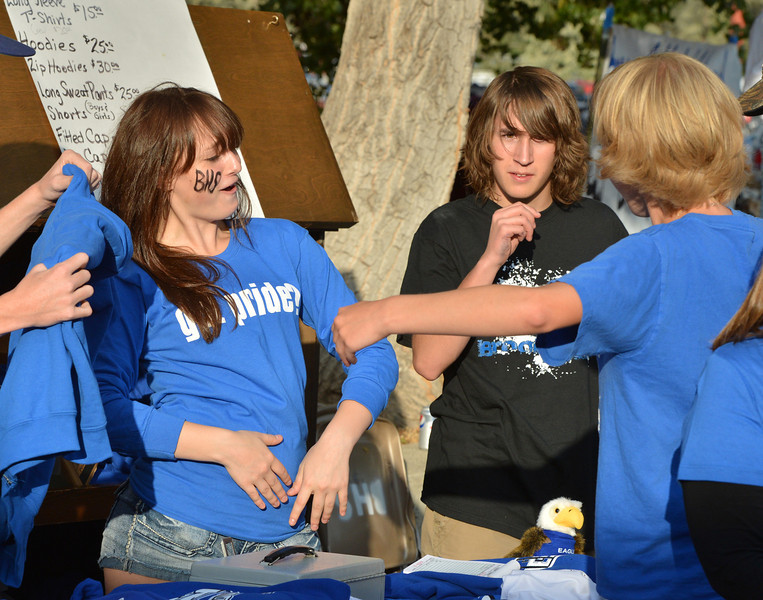 Junior Sabrina Spann, left, makes a positive comment to a customer while selling Broomfield High Spirit Gear at the tailgate party prior to the Broomfield vs. Legacy football game at Elizabeth Kennedy Stadium on Friday.<br /> September 7, 2012<br /> staff photo/ David R. Jennings
