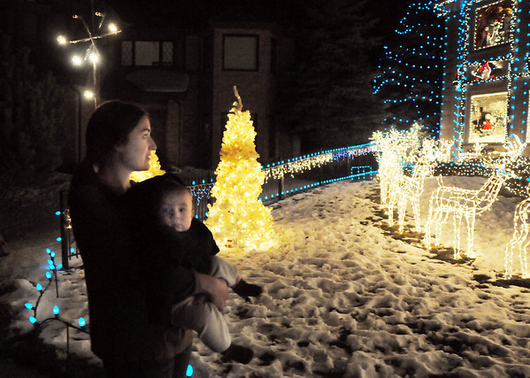 Pamela Yaden, a Tincup Circle neighbor, holds her son Avery, 8 months-old to look at the 13941 Tincup Circle holiday lighting display.<br /> <br /> December 13, 2009<br /> Staff photo/David R. Jennings