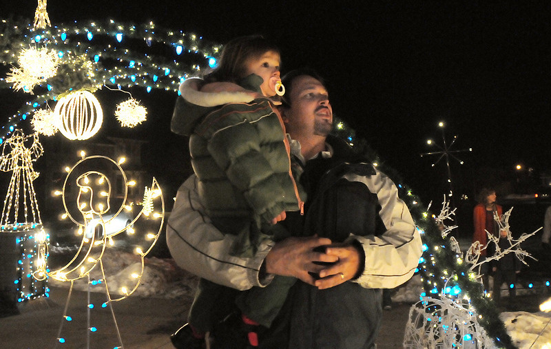 Brian Robertson holds his daughter Kayanne, 2, as they take in the 13941 Tincup Circle lighting display.<br /> <br /> December 13, 2009<br /> Staff photo/David R. Jennings