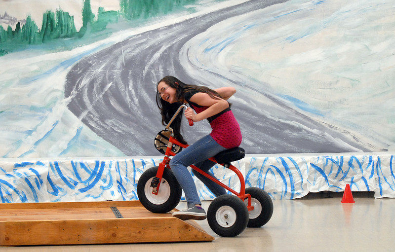 Camille Laufasa-Duncan, 12, rides a tricycle in the Ice Road Truckers room while attending the open house for JAM, Just After Midnight, after prom party at Broomfield High School on Saturday.<br /> April 16, 2011<br /> staff photo/David R. Jennings
