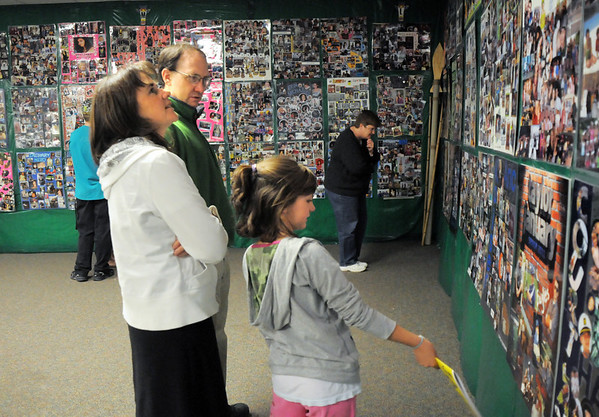 Jesse and Janela Karlson with their daughter Lydia, 9, look at senior posters including their older daughter Madeline while attending the open house for JAM, Just After Midnight, after prom party at Broomfield High School on Saturday.<br /> April 16, 2011<br /> staff photo/David R. Jennings