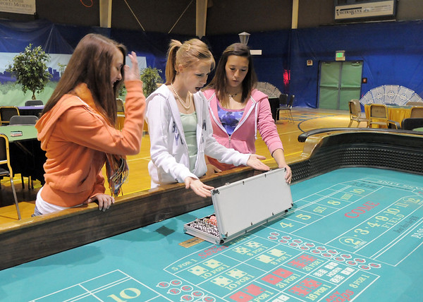 Emma Movick, 18, Mariah Hayden, 15, and Rebecca Rosenblum, 15, check out chips on the craps table in the Celebrity Poker room during  the open house for JAM, Just After Midnight, after prom party at Broomfield High School on Saturday.<br /> April 16, 2011<br /> staff photo/David R. Jennings