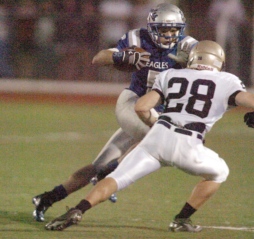 BE0919FOOT03<br /> Dan Geubelle, Broomfield, carries the ball tries to avoid the tackle by Zach Wilson, Legacy, during Saturday's cross town game at Elizabeth Kennedy Stadium..<br /> <br /> September 11, 2010<br /> staff photo/David R. Jennings