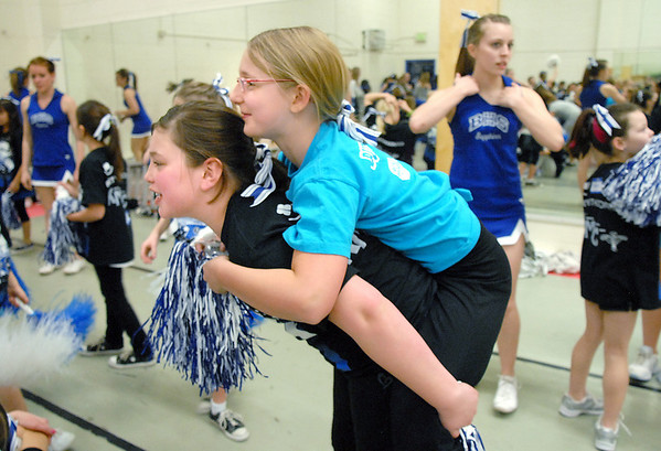 Annemarie Abeyta, 10, carries Ashley Haman, 10, after the Lil' Poms perfromed at halftime of the  Broomfield Girls basketball game at Broomfield High on Friday. <br /> February 10, 2011<br /> staff photo/David R. Jennings