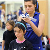 Broomfeild Pom Veda Magagna puts a ribbon in Anna Rehak's hair during the Lil' Poms clinic, a fundraiser for the pom squad, at Broomfield High on Friday. <br /> February 10, 2011<br /> staff photo/David R. Jennings
