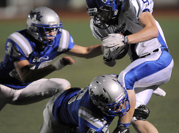 Longmont's DJ Fowler is tackled by Broomfield's  Lee Cannon and  Gian Panicucci during Friday's game at Elizabeth Kennedy Stadium.<br /> October 21, 2011<br /> staff photo/ David R. Jennings