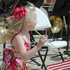 Lauren Johnson, 5 1/2, from Scottsbluff, Nebraska, runs carrying a flag past the Colorado National Guard 101st Army Band during the Broomfield Veterans Memorial Museum Memorial Day Picnic at the Broomfield County Commons Park on Monday. Johnson's father plays in the band<br /> May 30, 2011<br /> staff photo/David R. Jennings