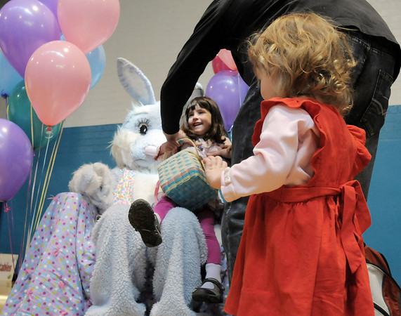 Taylor Portillo, 4, has help from her father, Jon, onto the lap of Flopsy the Bunny while her sister Alana, 2, waits her turn during the preschool Easter Party at the Broomfield Community Center on Thursday.<br /> <br /> April 21, 2011<br /> staff photo/David R. Jennings