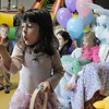 Taylor Portillo, 4, looks at her egg she got from Flopsy the Bunny while Maren Zickefoose, 3, has her picture taken during the preschool Easter Party at the Broomfield Community Center on Thursday.<br /> <br /> April 21, 2011<br /> staff photo/David R. Jennings