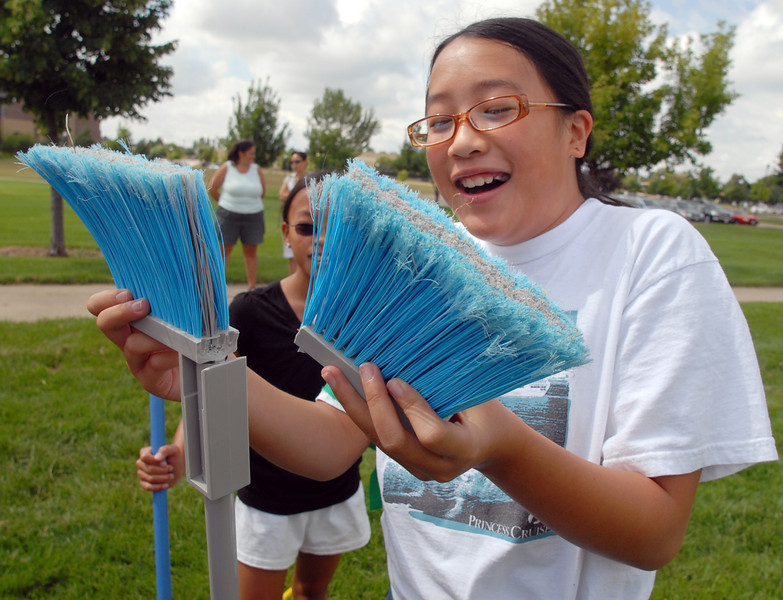 Jennifer Mah, 11, holds the broken parts of her broom during Mamie Doud Eisenhower Public Library's Quidditch Cup match at Community Center Park on Wednesday.  <br /> <br /> July 29,2009<br /> staff photo/David Jennings