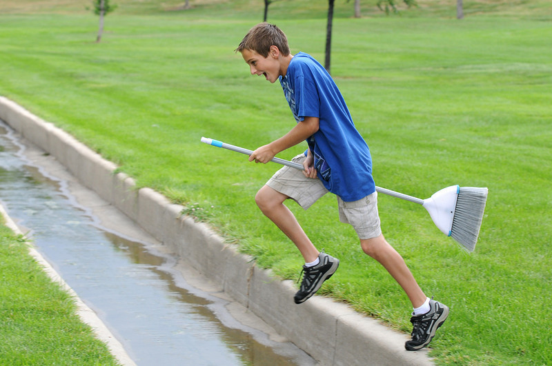 Tanner Heibert, 12, uses his broom to fly over a ditch after playing a quidditch game during Mamie Doud Eisenhower Public Library's Quidditch Cup match at Community Center Park on Wednesday.   <br /> July 29,2009<br /> staff photo/David Jennings