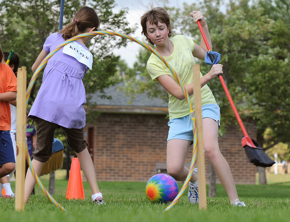 "Elise Steichen, 12, right, works to get the ""quaffle"" ball through one of three hoops while Aubrey Garrick, 12, defends the goal during Mamie Doud Eisenhower Public Library's Quidditch Cup match at Community Center Park on Wednesday. <br /> July 29,2009<br /> staff photo/David Jennings"