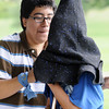 "Carlos Sobrebilla, 16, puts the ""sorting hat"" over Tanner Hiebert, 12, during Mamie Doud Eisenhower Public Library's Quidditch Cup match at Community Center Park on Wednesday.   <br /> July 29,2009<br /> staff photo/David Jennings"
