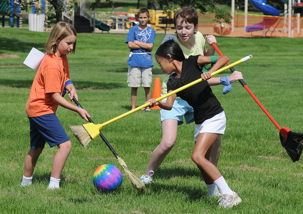 "Sophie Lehmann, 10, left, Monica Mah, 10, and Elise Steichen, 12, battle for the ""quaffle"" during Mamie Doud Eisenhower Public Library's Quidditch Cup match at Community Center Park on Wednesday.  Seventeen participants played several matches and answered trivia questions for the cup which was won by the Slytherin team by 2 points over Ravenclaw. <br /> July 29,2009<br /> staff photo/David Jennings"