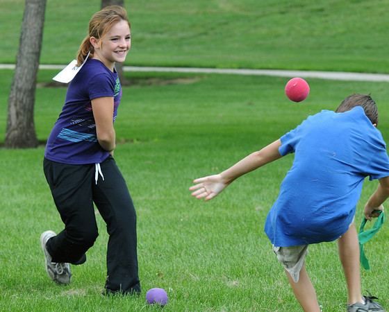 """Aubrey Garrick, 12, left, throws a """"bludger"""" ball at Tanner Hiebert 12, to freeze him during Mamie Doud Eisenhower Public Library's Quidditch Cup match at Community Center Park on Wednesday. <br /> July 29,2009<br /> staff photo/David Jennings"""
