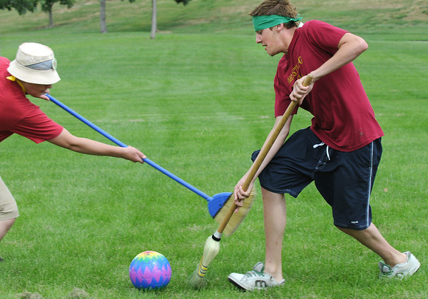 "James Ivey, 19, right, Slytherin, and Nate Fulton, 15, Hufflepuff, battle for control of the ""quaffle"" during Mamie Doud Eisenhower Public Library's Quidditch Cup match at Community Center Park on Wednesday.  <br /> <br /> July 29,2009<br /> staff photo/David Jennings"