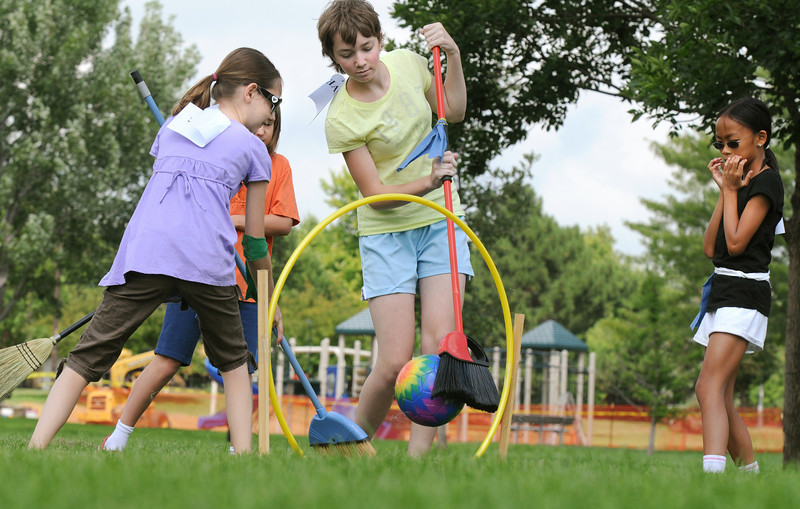 "Elise Steichen, 12, center, moves to put the ""quaffle"" ball through one of three goals while Aubrey Garrick, 12, defends the goal and Monica Mah, 10, right, watches during Mamie Doud Eisenhower Public Library's Quidditch Cup match at Community Center Park on Wednesday.  The 17 participants played several matches and answered trivia questions for the cup which was won by the Slytherin team by 2 points over Ravenclaw. <br /> July 29,2009<br /> staff photo/David Jennings"
