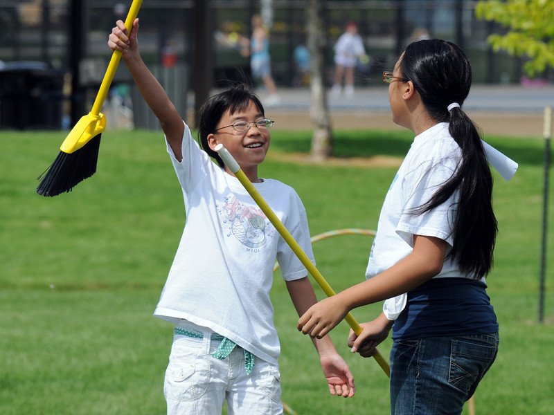 Nicole Mah. 10. left, cheers with her sister Jennifer Mah, 11, after scoring 10 points for a goal during Mamie Doud Eisenhower Public Library's Quidditch Cup match at Community Center Park on Wednesday.  <br /> July 29,2009<br /> staff photo/David Jennings