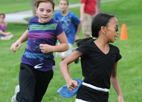 Seeker Kalei Rhodes, 11, left, chases after the snitch, Monica Mah, 10, during Mamie Doud Eisenhower Public Library's Quidditch Cup match at Community Center Park on Wednesday.  The first seeker who catches the snitch flag wins the game for their team.<br /> July 29,2009<br /> staff photo/David Jennings