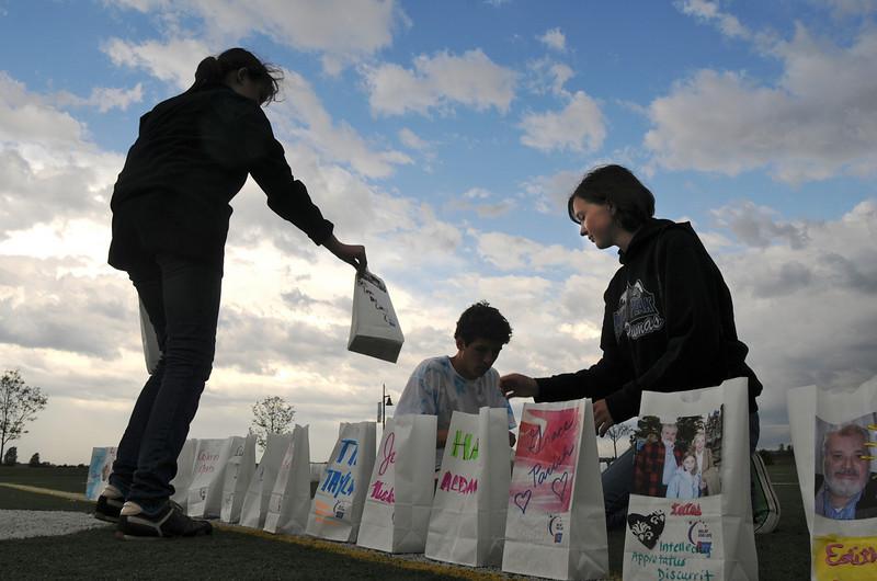Peak to Peak students Elena Lopez Del Carril, 12, left,  Oscar Jacob, 18 and Samantha Cole, 16, help set up luminarias around the championship field for Friday's 10th Relay for Life Broomfield fundraiser for the American Cancer Society at the Broomfield County Commons.<br /> <br /> <br /> June11, 2010<br /> Staff photo/David R. Jennings