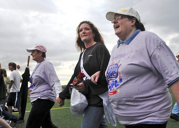 Dixie Feld, left, Rebecca Moore and her mother Tina Desautels walk the survivors lap on Friday at the 10th Relay for Life Broomfield fundraiser for the American Cancer Society at the Broomfield County Commons.<br /> <br /> <br /> June11, 2010<br /> Staff photo/David R. Jennings
