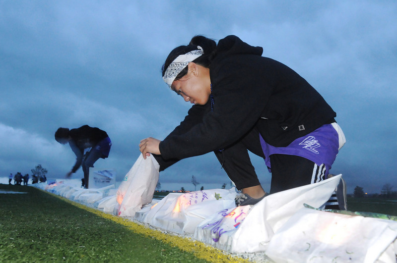 Peak to Peak students Erica Tran, 15, right, and Samantha Cole, 16, put lights in rain soaked luminarias during Friday's 10th Relay for Life Broomfield fundraiser for the American Cancer Society at the Broomfield County Commons.<br /> <br /> <br /> June11, 2010<br /> Staff photo/David R. Jennings