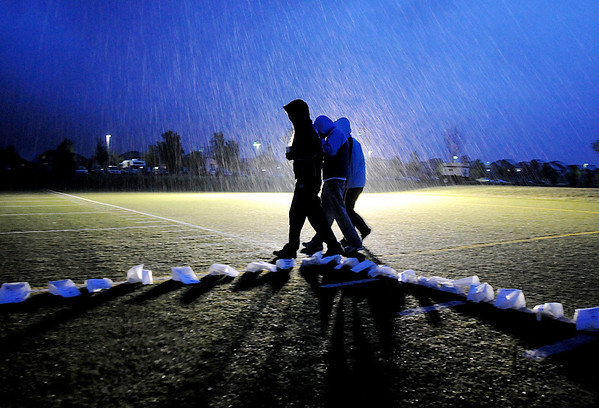 Participants brave the rain as they walk past the luminarias in the rain on Friday at the 10th Relay for Life Broomfield fundraiser for the American Cancer Society at the Broomfield County Commons.<br /> <br /> <br /> June11, 2010<br /> Staff photo/David R. Jennings