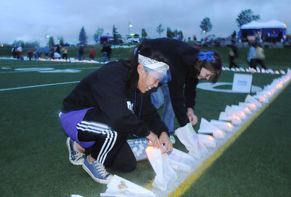 Peak to Peak students Erica Tran, 15, left, and Samantha Cole, 16, put lights in the rain soaked luminarias during Friday's 10th Relay for Life Broomfield fundraiser for the American Cancer Society at the Broomfield County Commons.<br /> <br /> <br /> June11, 2010<br /> Staff photo/David R. Jennings