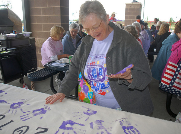 Bernie DiFalco, a 38 year survivor of cancer,  puts her hand print on the survivor's banner before Friday's 10th Relay for Life Broomfield fundraiser for the American Cancer Society at the Broomfield County Commons.<br /> <br /> <br /> June11, 2010<br /> Staff photo/David R. Jennings