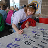 Cancer survivor Shelle Ferraro autographs her hand print on the survivors banner before Friday's 10th Relay for Life Broomfield fundraiser for the American Cancer Society at the Broomfield County Commons.<br /> <br /> <br /> June11, 2010<br /> Staff photo/David R. Jennings