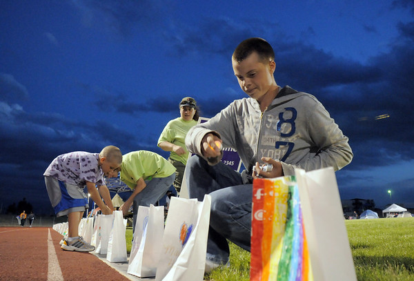 Isaiah Feeley 14, right places lights into the luminarias with fellow Boy Scouts from Troop 2247 during the Broomfield Relay for Life at Holy Family High School on Saturday.<br /> June 10, 2011<br /> staff photo/David R. Jennings