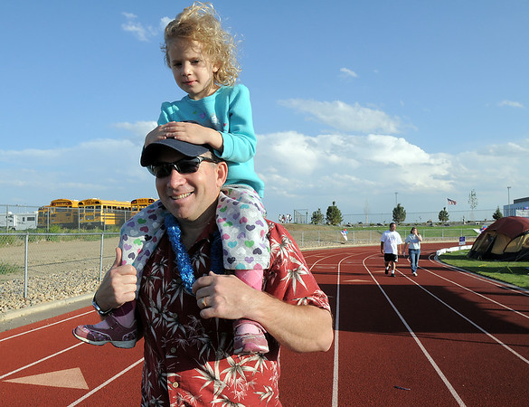 Patrick Lilienthal carries his daughter Emily, 4, on his shoulders as they walk around the track during the Broomfield Relay for Life at Holy Family High School on Saturday.<br /> June 10, 2011<br /> staff photo/David R. Jennings