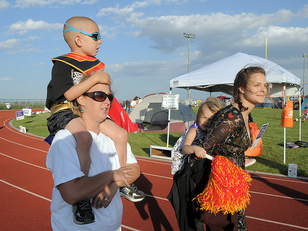 Cancer survivor Logan Moore, 4 1/2, is carried by his relative Christina Lassen while Chloe Lassen, 3 is carried by Chelsea Lassen as they walk around the track during the Broomfield Relay for Life at Holy Family High School on Saturday.<br /> June 10, 2011<br /> staff photo/David R. Jennings