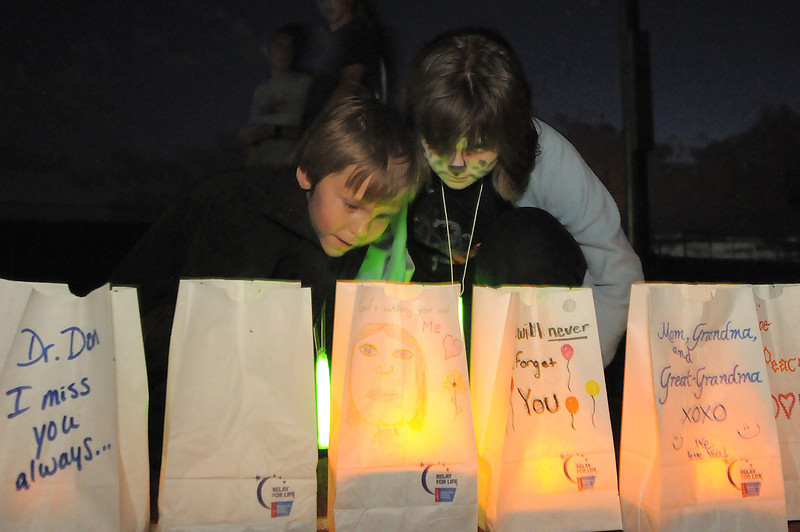 Cody Wassenburger, 6, left, and his sister Mackenzie, 9, look at their grandmother's luminaria a cancer survivor during the Broomfield Relay for Life at Holy Family High School on Saturday.<br /> June 10, 2011<br /> staff photo/David R. Jennings